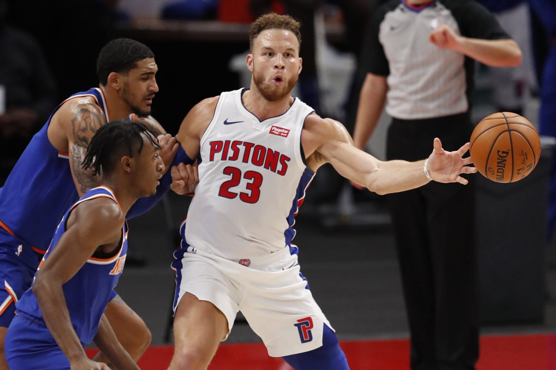 Dec 13, 2020; Detroit, Michigan, USA; Detroit Pistons forward Blake Griffin (23) passes the ball as he is covered by New York Knicks forward Obi Toppin (1) during the second quarter at Little Caesars Arena. Mandatory Credit: Raj Mehta-USA TODAY Sports