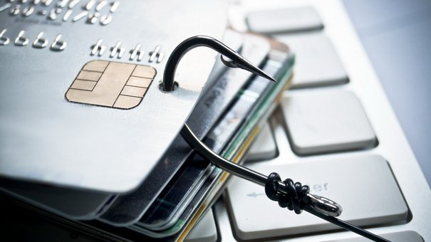 Phishing - a credit card with a fish hook trying to steal personal data on a computer keyboard / financial data theft