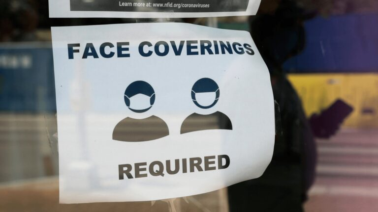 A visitor wearing a mask to protect against the spread of COVID-19 passes a sign requiring masks, Tuesday, July 7, 2020, in San Antonio. Texas Gov. Greg Abbott has declared masks or face coverings must be worn in public across most of the state as local officials across the state say their hospitals are becoming increasingly stretched and are in danger of becoming overrun as cases of the coronavirus surge. (AP Photo/Eric Gay)